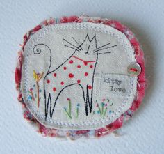 Here we have a handmade brooch. I have screen printed and hand painted my Kitty design onto linen. With hand embroidered flowers. A lovely old button