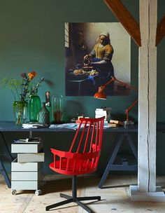 Industrial style home office with a dark green wall, red chair, dark metal desk