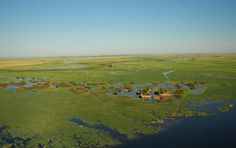 The photo features a small water-logged village in the Caprivi Strip, Namibia, with a lush landscape surrounding it, albeit flooded too - natural flooding