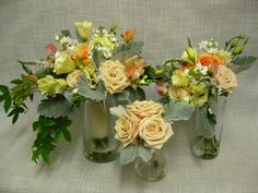Soft summer toned Trio of wedding bouquets. Created with Sahara roses, Finesse roses, white stock, lysimachia, yellow lisianthus, dusty miller, white freesia peach sweet pea and passioin flower vine accents in the brides bouquet.