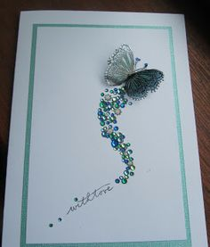 """""""Less Is More"""" Project.  Stamped and Flourish onto White Card Stock Paper. Colored Butterfly with Copics and Glitter pens.  Butterfly Image was then Stamped onto acetate, then was cut out then placed over the first image. Then Gems were Glued Over the Flourish."""