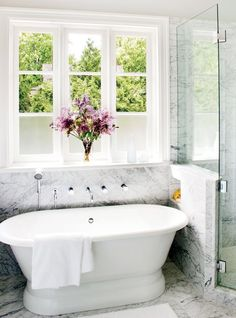 bathroom with stand in tub, marble floors and a large encasement window