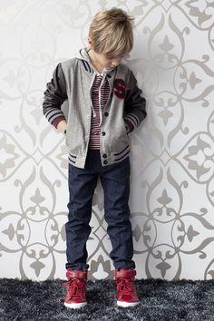 El chico lleva una chaqueta gris y negra, los jeans azules, y los zapatos rojos.
