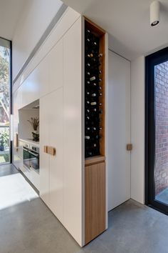 This House Addition Has Forms Arranged In A Tetris-Like Configuration Kitchen Ideas - This modern kitchen has a large wood peninsula, minimalist white cabinets, oversized hardware, and built-in wine s Wine Storage Cabinets, Kitchen Storage, Modern Kitchen Design, Interior Design Kitchen, Bar Sala, Kitchen Pictures, Kitchen Ideas, Pantry Design, Home Additions