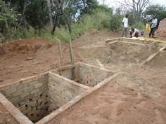 7. The brick structure is split into two with another wall down the middle, effectively making two latrine pits side-by-side.