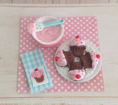 Miniature Chocolate Cherry Cupcake Cookies, A Bowl Of Frosting, And A Cute Kitchen Towel With A Cupcake