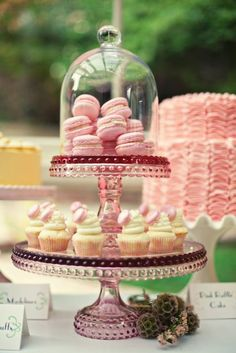 Pink Macarons and cupcakes on a cake stand.