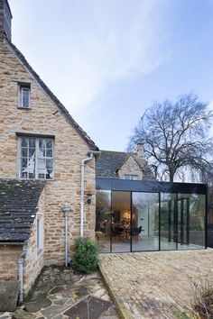 A modern glass kitchen extension built onto this listed cottage in the countryside has created a luxurious open plan living space, adding a modern touch to the old brick cottage...