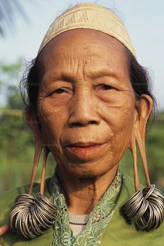 DAYAK, MALAYSIA. Sarawak, Borneo, South East Asia. | Portrait of Dayak woman with distended earlobes and earnings. | © Nigel Dickson