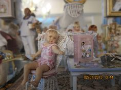 Susan's adorable resin blond toddler reaching for some cookies on the table. Louise Glass