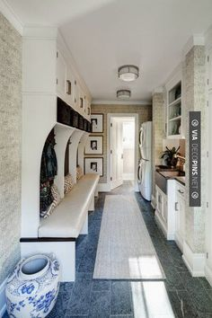 Love the combination of the mud room  laundry room.black and white framed photos in the utility/laundry area