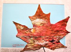 A maple leaf with a blazing sunset