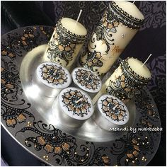 White candles with black henna designs
