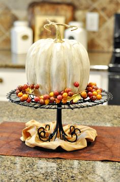 pumpin centerpiece...spray paint pumpkins white, then brush with watered-down metallic paint