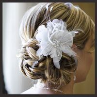 I love a low updo with a flower.  This would be cute for all the bridesmaids. Needs some purple and turquoise