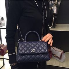 The Coco Handle Bag comes with a front flap, a handle on top and intertwined chain/leather shoulder strap. It features a trapezoid design with the interlock CC closure and ruthenium hardware. http://www.luxtime.su/chanel-small-coco-handle-bag-c92991b-black-bk