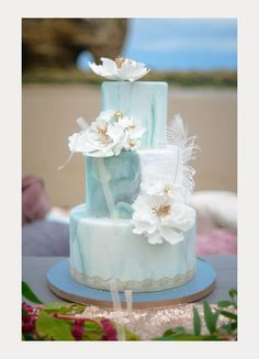 Light teal three tier marble wedding cake with gold lace accent and white sugar flowers.