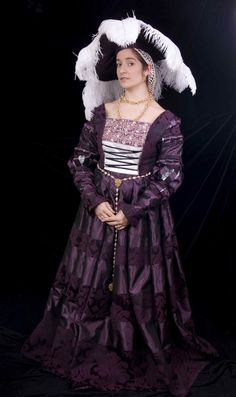 Sybilla of Cleves - Originally based on the portrait at right of Sybilla of Cleves, this German renaissance gown is made of purple brocade with purple taffeta. The skirt features rolled pleats. The brustfleck (bustline trim) is beaded, embroidered, silk metallic trim which was hand-dyed to match the gown. The gown laces closed in the front through rings sewn into the bodice. Presented by 'Fashions in Time'.