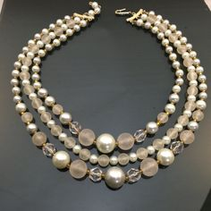 Beautiful Vintage Faux Pearl & Glass Bead Multi-Strand Choker Necklace. This tasteful choker with reflective glass, pearlescent and matte plastic beads, make up a stunning combination for this 1950s style multi-strand necklace and would be stunning on either a light and dark outfit. Nice Item! Length of 14 Sold As-Is.