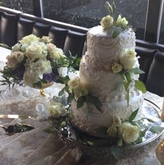 3 tired wedding cake decorated with a filigree design adorned with white roses and greenery. Cake designed by Flowers by the Bunch