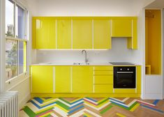 Multicoloured herringbone patterns cover sections of parquet flooring in these London apartments renovated by Alma-nac, influenced by record sleeve designs. Planchers En Chevrons, Yellow Kitchen Cabinets, Kitchen Yellow, Floors Kitchen, Kitchen Units, Küchen Design, House Design, Apartment Renovation, London Apartment