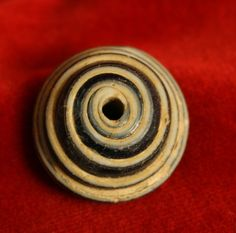 "Roman Glass Spindle Whorl  Origin: Israel  Circa: 100 AD to 300 AD   Dimensions: .9375"" (2.4cm) wide   Style: Roman Period"