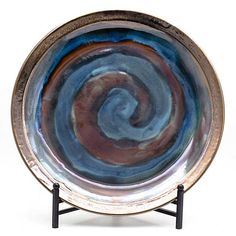 Ceramic and a fine metallic finish combine to create a look that is both eye-catching and humble, modern and traditional. Muted blue and brown tones swirl across the entirety of the plate, finished with a rustic metallic rim that ties the colors toge Plate Stands, Plate Sets, Decorative Bowls, Decorative Pillows, Plate Design, Rustic Style, Accent Pieces, Mantle, Decorative Accessories