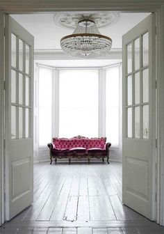 So simple, yet so effective. Pink velvet couch on stage in this white, traditional room.