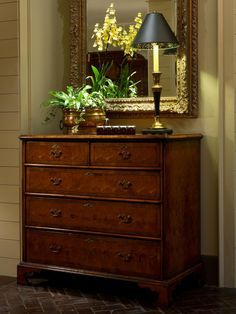 An antique chest takes the place of pride in this entry hall. A beautiful orchid flower arrangement is cleverly placed in front of a mirror, making the arrangement appear twice as large.