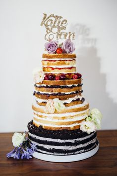 Naked rustic wedding cake with different flavor cakes and fillings, decorated with flowers | Image by Liam Smith Photography