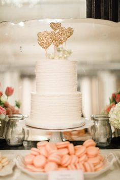 Simple white cake, decorated with gold-coloured love hearts. Cake made by Layered Cake Shop. Photo courtesy of Style Me Pretty.