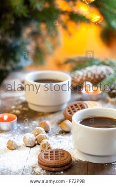 Download this stock image: Coffee, tangerines, cookies and nuts in Christmas decor with Christmas tree, nuts and apples on colorful background bokeh - F72P9B from Alamy's library of millions of high resolution stock photos, illustrations and vectors.