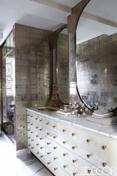 The master bath is sheathed in glass tiles by Ann Sacks, the parchment-covered vanity and mirrors are custom made, and the sink and fittings are by Waterworks.
