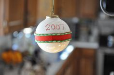 A glass ball and a ceramic pen and some ribbon.  I like the simplicity of this ornament.  Family ornament 2007.