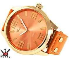 Γυναικείο ρολόι, σε ροζ χρυσό και πορτοκαλί, με μεγάλα νούμερα στο εσωτερικό του. Λουράκι δερματίνης σε πορτοκαλί χρώμα. Διάμετρος καντράν 50 mm.