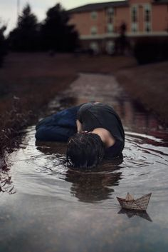 The story within this photo. The grim colors, the toy paper boat, the haunting trees, to the soaking boy laying in the water. Story Inspiration, Writing Inspiration, Character Inspiration, Robert Frank, Arte Obscura, Foto Art, Art Photography, Sadness Photography, Scene