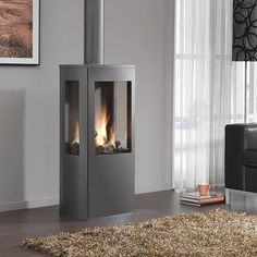 The DRU Trio freestanding gas fire combines the nostalgia of a rustic gas stove with innovative technology. Offering a balanced flue model in archetypal anthracite finish with a striking, 3-sided log fire display that will produce a comforting radiance all around your living room. #gas #fire #fireplace #DRU #york #yorkshire