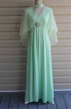 This is such a dreamy minty misty maxi dress with its sheer upper overlay that extends outward to angel wings over a sleeveless bodice and