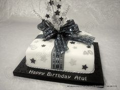 Combine a present and a cake to give one. A single tier parcel celebration cake covered in white icing on a black iced board decorated with simple stars and age in black and silver. Tied with a large sparkle ribbon and bow, and explosive starburst topper