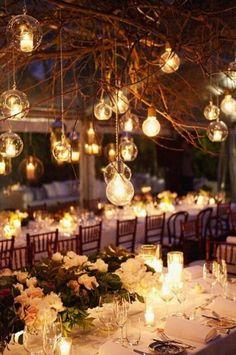 Ideas para decorar el salon de bodas con luces combinando velas y bombillas sin pantalla y ramas secas.