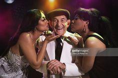Foto de stock : Hispanic women kissing senior man in nightclub