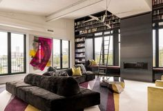 Custom Industrial Chic by Les Ensembliers Bookcase, ladder, window seats, fireplace: this room has everything!