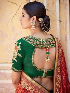 Latest blouse styles   new blouse styles to love   latest blouse designs for Indian brides   Indian bride with beautiful twisted braid with baby's breath flowers   open back cutout style blouse in green with a pom pom hanging on the back