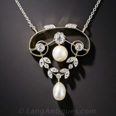 Edwardian Diamond and Pearl Pendant. Elegantly hand crafted in platinum over 18K gold, a classic and curvaceous Edwardian pendant necklace aglitter with three bright white old mine-cut diamonds and a pair of dangling (perhaps natural) pearls separated by a diamond-set garland. Delightful. Circa 1910. 1 and 3/16 by 15/16 inches, the platinum chain measures 16 inches.