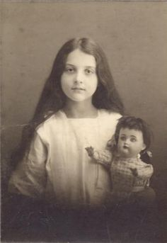 Antique photo of young girl with doll.