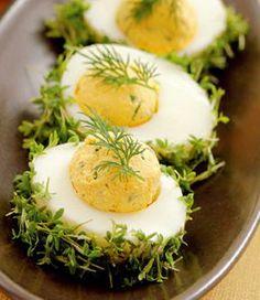Jajka obierz, przekrój na pół, wyjmij żółtka, rozgnieć je widelcem, połącz z posiekanym szczypiorem i koperkiem. Wymieszaj ze śmietaną i musztardą, przypraw do smaku. Wypukłą część białek posmaruj majonezem i obtocz w listkach rzeżuchy (powstaną zielone koszyczki). Z masy żółtkowej uformuj kulki,włóż je w zagłębienia. Udekoruj koperkiem. I Love Food, Good Food, Yummy Food, Easter Recipes, Appetizer Recipes, Tapas, Cooking Recipes, Healthy Recipes, Snacks Für Party