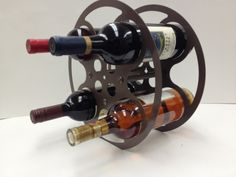 This wine rack was crafted from a 16mm film reel, and was finished with a Brown wrinkle finish.     Fits most bottles and wine bottle