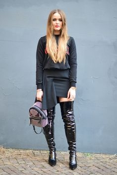 An all-black outfit with thigh-high patent leather boots.