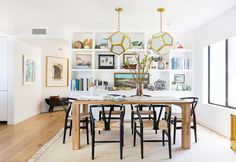 Elegant dining space with large chandeliers, a wooden table, and wishbone chairs