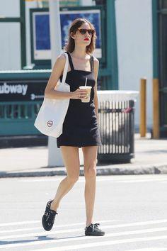 Alexa Chung : minivestido negro, zapatillas negras, de Superga; bolso de tela, de AG Jeans y gafas de sol de carey con forma de ojo de gato.